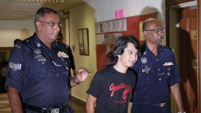 Activist Adam Adli, center, smiles before being released on bail at a court house in Kuala Lumpur, Malaysia, Thursday, May 23, 2013. Prosecutors filed a sedition charge Thursday against a student activist who urged Malaysians to engage in street protests against the government over claims of election fraud. (AP Photo/Vincent Thian)