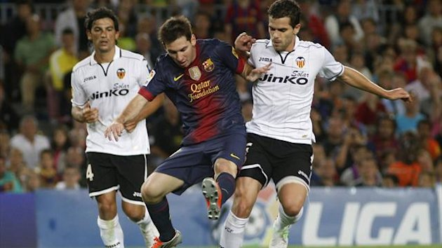 Barcelona's Lionel Messi controls the ball against Valencia's Fernando Gago