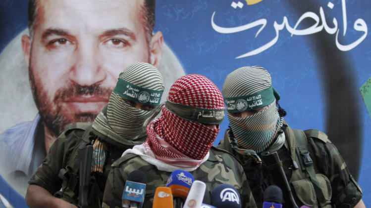 "A Hamas militant talks during a press conference in Gaza City, Thursday, Nov. 22, 2012. Gazans are celebrating a cease-fire agreement reached with Israel to end eight days of the fiercest fighting in nearly four years constricting the Gaza Strip. The poster behind him reads: ""Gaza won"" and shows the picture of Ahmed Jabari,a Hamas leader assassinated on Nov.14, setting off the last round of fighting between Israel and Hamas . (AP Photo/Hatem Moussa)"