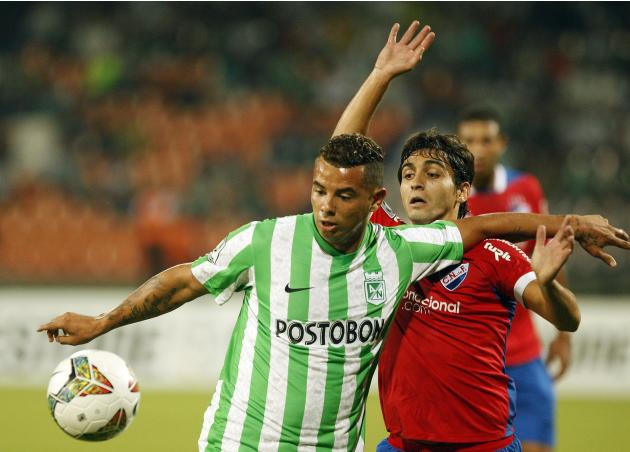 Cardona of Atletico Nacional and Calzada of Nacional fight for the ball during their Copa Libertadores soccer match in Medellin