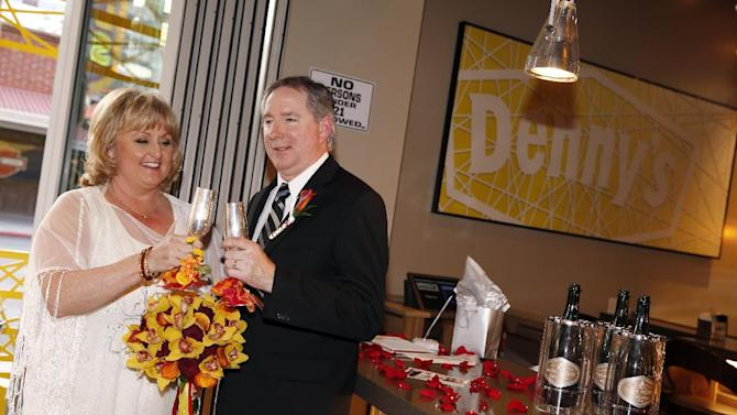IMAGE DISTRIBUTED FOR DENNY'S - Nancy Keller, left, and Steven Keller toast following their wedding ceremony, the first at Denny's on Fremont on Wednesday, April 3, 2013 in Las Vegas. Denny's selected the Kellers, long-time food enthusiasts, to be the first couple to walk down the aisle in the unique wedding location. (Isaac Brekken/AP Images for Denny's)