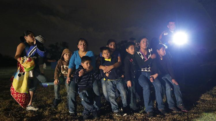 FILE - In this June 25, 2014 file photo, a group of immigrants from Honduras and El Salvador who crossed the U.S.-Mexico border illegally are stopped in Granjeno, Texas. Many of the immigrants recently flooding the nation's southern border say they're fleeing violent gangs in Central America. These gangs were a byproduct of U.S. immigration and Cold War policies, specifically growing from the increase in deportations in the 1990s. With weak dysfunctional governments at home, U.S. street gang culture easily took hold and flourished in these countries. (AP Photo/Eric Gay)