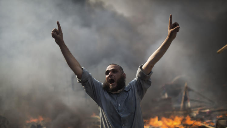 A supporter of ousted Islamist President Mohammed Morsi shouts during clashes with Egyptian security forces in the Nasr City district of Cairo Wednesday, Aug. 14, 2013. Violence spread across much of Egypt after police cleared two encampments of Morsi's supporters, showering protesters with tear gas as the sound of gunfire rang out. At least 149 people were killed nationwide, many of them in the assaults on the protest vigils. (AP Photo/Manu Brabo)