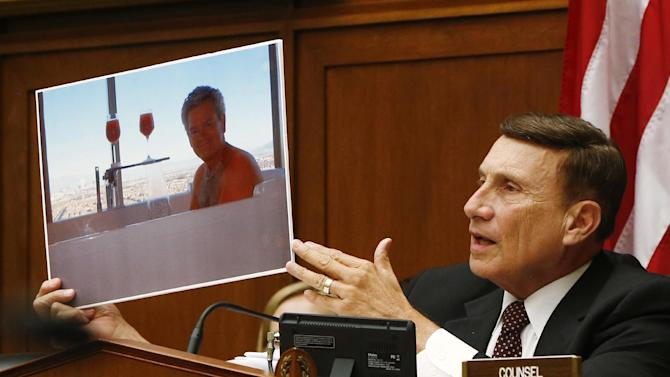 House Oversight and Government Reform Committee member Rep. John Mica, R-Fla., holds up a picture of a GSA employee in a hot tub as he questions witnesses on Capitol Hill in Washington, Thursday, June 6, 2013, during the committee's hearing regarding IRS conference spending. (AP Photo/Charles Dharapak)