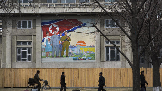 North Korean pedestrians walk on a sidewalk past a large nationalist painting in Pyongyang, North Korea on Wednesday, April 10, 2013. (AP Photo/David Guttenfelder)
