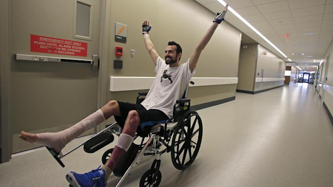 """In this Wednesday, May 22, 2013 photo, Boston Marathon bombing survivor Pete DiMartino, of Rochester, N.Y., raises his arms after completing a physical therapy session at the Spaulding Rehabilitation Hospital in Boston. DiMartino was injured in an explosion near the finish line, which blew away much of one leg and burned the other. """"I don't want anybody feeling sorry for me,"""" he said. """"... I want people to see that this has made me a better person and I want people to become better people through what they see through me."""" (AP Photo/Charles Krupa)"""