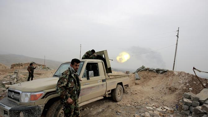 In this Thursday Jan. 29, 2015 photo, a Kurdish peshmerga fighter fires a weapon towards an Islamic State Group position 500 meters, or half a mile away,  overlooking the town of Sinjar northern Iraq. Kurdish forces in recent weeks have retaken parts of the strategic Iraqi town of Sinjar, whose Yazidi population was driven out in a humanitarian disaster last year that triggered U.S. intervention. But disagreements among Kurdish factions makes the hold on the town seem shaky and is threatening the wider fight against Islamic state militants. (AP Photo/Bram Janssen)