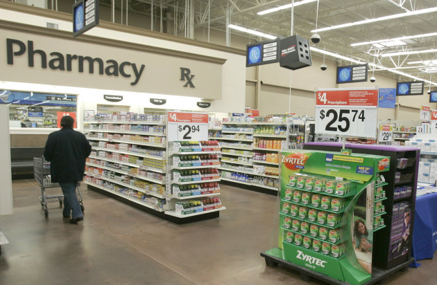 FILE - In this Feb. 20, 2008, file photo, a shopper walks toward the pharmacy at a Little Rock, Ark., Wal-Mart store. A study says seniors in seven of the 10 most popular Medicare prescription drug plans will be hit with double-digit premium hikes next year if they don't shop for a better deal. The report by Avalere Health is a reality check against the Obama's administration's upbeat pronouncements. Back in August 2012, officials had announced that the average premium for basic prescription drug coverage would stay the same in 2013, at $30 a month. (AP Photo/Danny Johnston, File)