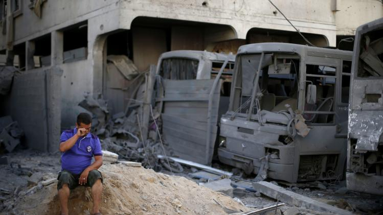 A Palestinian sits next to buses that witnesses said were destroyed during an Israeli airstrike in Gaza City