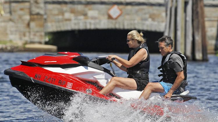 """FILE - In this July 2, 2012, photo Republican presidential candidate Mitt Romney, and wife Ann Romney jet ski on Lake Winnipesaukee in Wolfeboro, N.H. Romney's large family is at the center of his life _ and of his presidential campaign. At a time when nontraditional families have become the norm _ and when even the Romneys are watching """"Modern Family,"""" a popular sitcom that centers on unconventional family arrangements _ the Romney brood stands out. (AP Photo/Charles Dharapak, File)"""