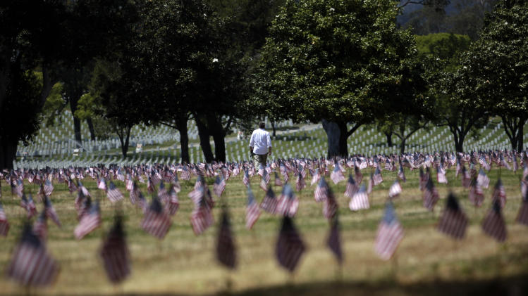 Documentary filmmaker Michael Prescott, center, pays his respects at the Los Angeles National Cemetery in the Westwood section of Los Angeles, Friday, May 25, 2012. (AP Photo/Jae C. Hong)