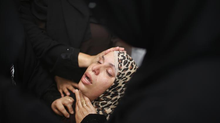 A relative of Palestinian members of Al-Batsh's family, who hospital officials said were killed in an Israeli air strike, mourns during their funeral in Gaza City