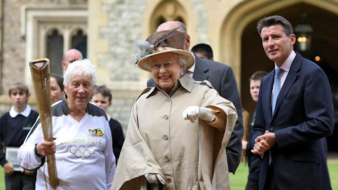 This image made available by LOCOG shows Queen Elizabeth II, center, and the Duke of Edinburgh, obscured, and Olympic chairman Sebastian Coe right, watch as Torchbearer 073 Gina Macgregor, left, holds the Olympic flame outside Windsor Castle, Windsor, England Tuesday July 10, 2012.    (AP Photo/Chris Radburn/LOCOG)