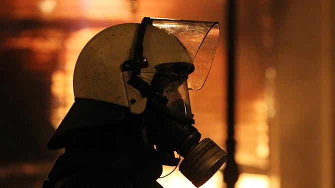 A riot police officer looks on as a branch of the Cosmote mobile company is ablaze during clashes in Athens, Sunday, Feb. 12, 2012. Protesters and police fought running battles in central Athens Sunday, as Greek lawmakers debated legislation that would introduce severe austerity measures to stave off bankruptcy. (AP Photo/Thanassis Stavrakis)