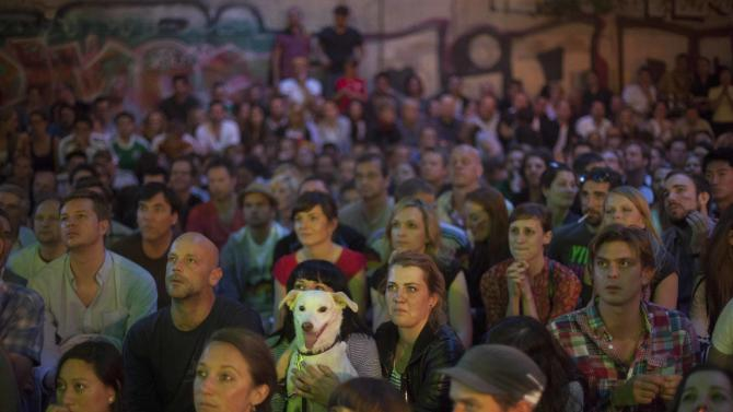 A dog sits between hundreds of German soccer fans a courtyard of a restaurant at Berlin's district Mitte during the screening of the Euro 2012 quarter final soccer match between Germany and Greece in Berlin, Friday, June 22, 2012. (AP Photo/Markus Schreiber)