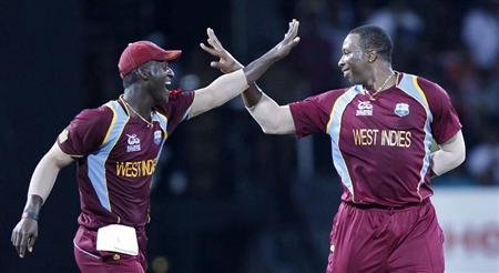 West Indies' Pollard celebrates with his captain Sammy after taking the wicket of Australia's Cummins during their Twenty20 World Cup semi-final cricket match in Colombo