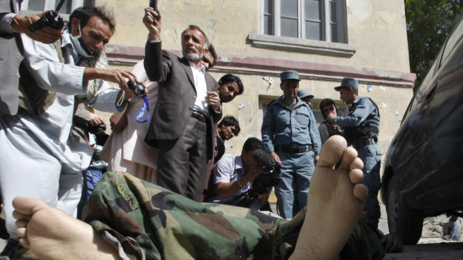 Afghan men take pictures of the remains of an attacker in Kabul, Afghanistan, Saturday, June 18, 2011. Men dressed in Afghan army uniforms stormed the police station near the presidential palace and opened fire said Mohammed Honayon, an eyewitness. President Hamid Karzai said Saturday that Afghanistan and the United States are engaged in peace talks with the Taliban, even as insurgents stormed a police station killing three people. (AP Photo/Gemunu Amarasinghe)