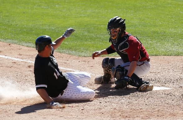 Chicago White Sox's Paul Konerko slides safely under the tag of Arizona Diamondbacks catcher Tuffy Gosewisch to score in the sixth inning during an exhibition baseball game in Glendale, Ariz., Saturday, March 8, 2014. (AP Photo/Paul Sancya)