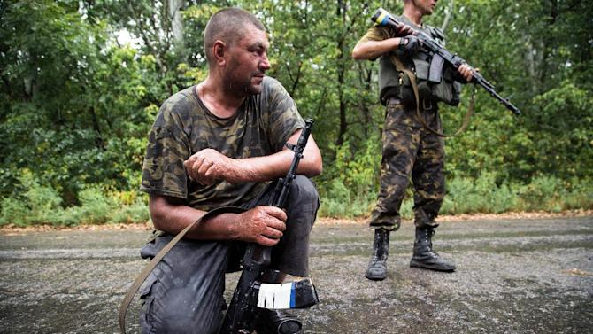 Ukrainian servicemen at a checkpoint in the Donetsk region, August 28, 2014. The prospect of a military confrontation between Ukraine and Russia has knocked market confidence