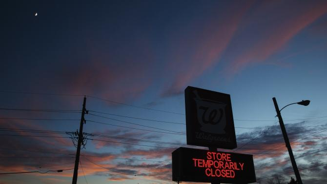 The Sun sets behind a Walgreens store sign on W. Florissant Ave. that remains closed due to looting during protests that erupted in reaction to the grand jury verdict in the Michael Brown shooting near Ferguson, Missouri