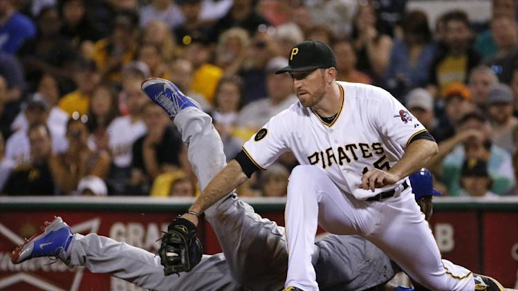 Los Angeles Dodgers' Yasiel Puig dives back to first safely as Pittsburgh Pirates first baseman Ike Davis takes the throw during the eighth inning of a baseball game against the Pittsburgh Pirates in Pittsburgh Wednesday, July 23, 2014. Puig pinch hit for pitcher Paul Maholm and was walked. The Pirates won 6-1. (AP Photo)