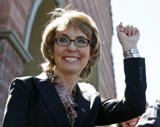 FILE - In this Wednesday, March 6, 2013 file photo, former U.S. Rep. Gabrielle Giffords smiles as she raises a fist pump to the crowd as she, husband Mark Kelly, and a number of other Tucson mass shoo