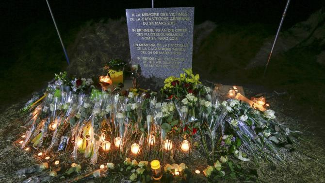 Flowers and candles surround the memorial with the inscription in four languages in the village of Le Vernet