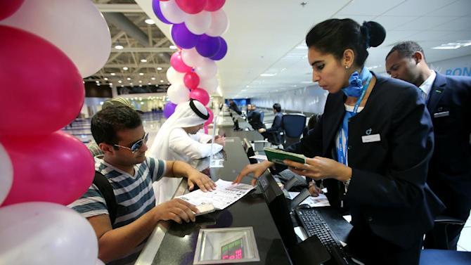 Passengers check-in at the newly opened Al Maktoum International Airport in Dubai, United Arab Emirates, Sunday, Oct. 27, 2013. The first passengers have arrived at Dubai's newest airport, part of the United Arab Emirates' plans to become a major air travel destination. The new airport is known by the code DWC for Dubai World Center. (AP Photo/Patrick Castillo, Emarat Al Youm)