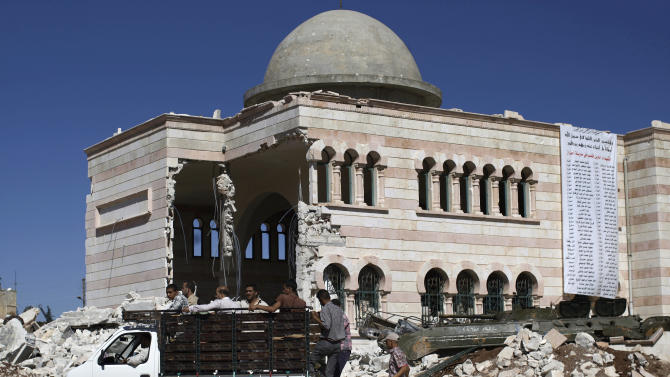 Syrian men stand on the back of a vehicle moving past a damaged mosque in the city of Azaz, on the outskirts of Aleppo, Syria, Wednesday, Aug. 22, 2012. (AP Photo/Muhammed Muheisen)
