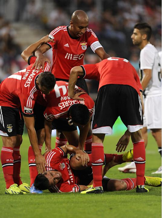 Benfica's players gather around Oscar Cardozo, below, after he was injured after scoring a goal against Vitoria Guimaraes in a Portuguese League soccer match at D. Afonso Henrique stadium in Guimaraes