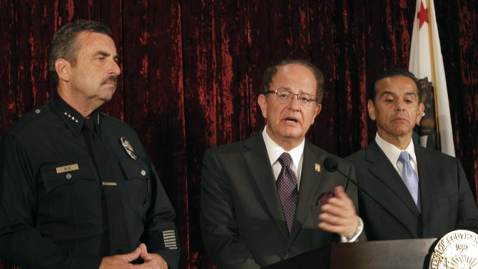 Los Angeles Police Chief Charlie Beck, left joins Los Angeles Mayor Antonio Villaraigosa, right as USC President C.L. Max Nikias answers questions during a news conference at the USC campus in Los Angeles on Thursday, April 26, 2012.  The University of Southern California and Los Angeles police say they will beef up security around the campus following the unsolved killings of two Chinese graduate students. On Thursday it was announced that the school will pay to put four more city police officers on patrol. In addition, Police Chief Charlie Beck says 30 more officers will be assigned to the division that handles the university. (AP Photo/Nick Ut)