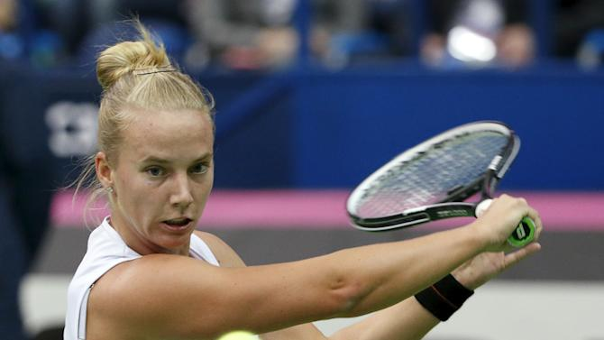 Richel Hogenkamp of the Netherlands hits a return against Russia's Svetlana Kuznetsova during their Fed Cup World Group tennis match in Moscow