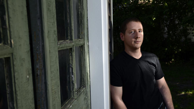 In this photo taken Wednesday, June 5, 2013, Justin Farman, a nursing student from Watertown in upstate New York, poses for a portrait at his Watertown apartment. Farman was diagnosed with a blood cancer last fall, when he was uninsured, and is now fending off collection agencies pursuing some of the approximately $50,000 in bills he has accumulated due to his illness. Huge list prices charged by hospitals are getting increasing attention, but a federal law meant to limit what the most financially vulnerable consumers can be billed doesn't seem to be making much difference. (AP Photo/Kevin Rivoli)
