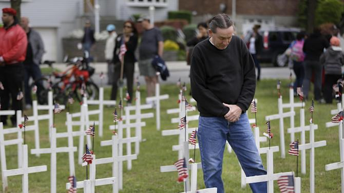 Joe Schulmann pauses in prayer over a cross bearing the name of his neighbor, Michael Wick, who was killed during the Vietnam War, at the College Point Memorial Day Parade in New York, Sunday, May 26, 2013. (AP Photo/Seth Wenig)
