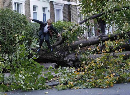A 13-year-old student jumps over a fallen tree as he makes his way to school in Islington, north London