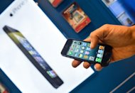 A customer is seen holding the new Apple iPhone 5 smartphone in a telephone operator's shop in Rome, Italy, on September 28. The new iPhone 5 broke records in its launch weekend with sales above five million but the figures were below some forecasts and pressured the company's share price