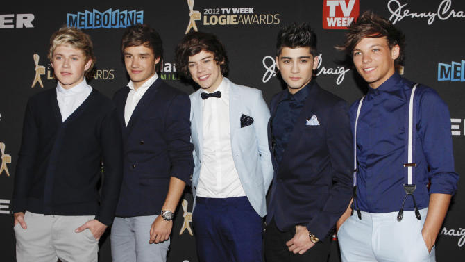 """FILE - This is a Sunday, April 15, 2012 file  photo of British boy-band One Direction arrive for the Logies, an Australian television industry awards night, in Melbourne, Australia. One Direction's latest single sums it up. """"Live While We're Young"""" is the first track off their second album, and the boys are happy to have it as a motto. The members of the British pop group admit they're making the most of being young, successful and extremely popular. (AP Photo/Paul Jeffers, File)"""
