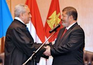 In this handout picture made available by the Egyptian presidency, Egyptian President Mohamed Morsi (R) shakes hands with Faruq Sultan, head of the presidential election commission, after taking the oath of office at his swearing-in ceremony at the Constitutional Court in Cairo