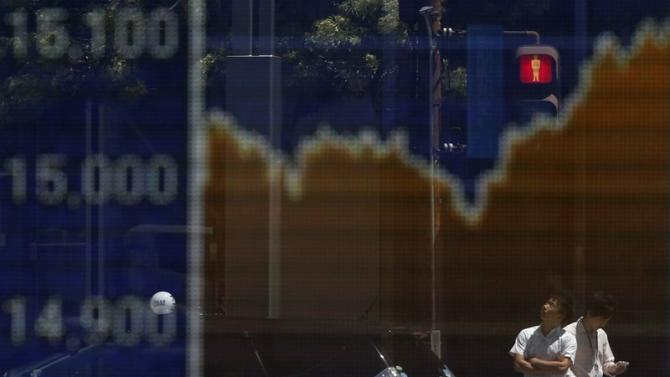 Man looks up as he is reflected on an electronic board displaying Japan's Nikkei average outside a brokerage in Tokyo