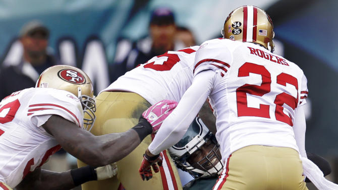 Philadelphia Eagles quarterback Michael Vick (7) is hit by San Francisco 49ers inside linebacker Patrick Willis (52), linebacker Ahmad Brooks (55) and cornerback Carlos Rogers (22) in the second half of an NFL football game Sunday, Oct. 2, 2011, in Philadelphia. (AP Photo/Julio Cortez)