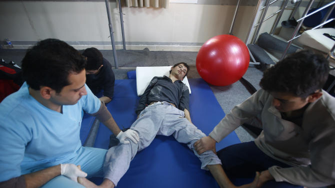 An injured Syrian man receives physical therapy at a small clinic near the Turkish-Syrian border in the southeastern city of Kilis