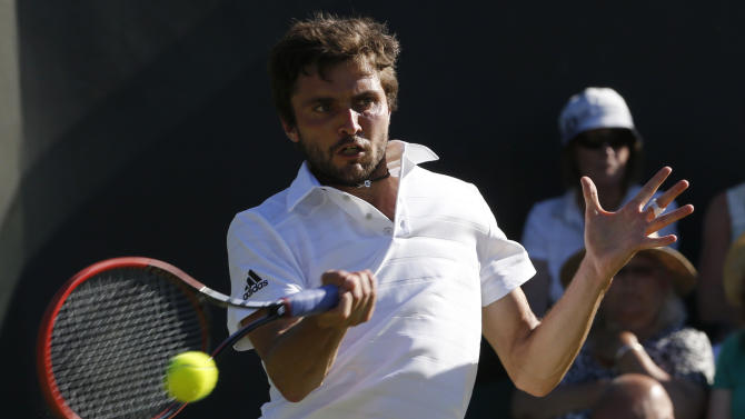 Gilles Simon of France hits the ball during his match against Nicolas Almagro of Spain at the Wimbledon Tennis Championships in London