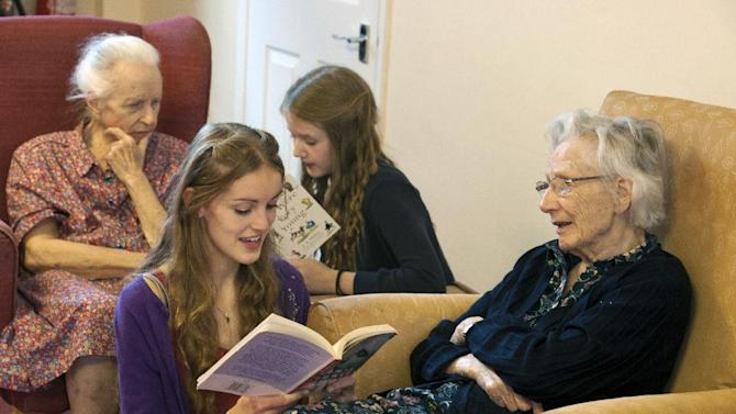 Volunteers from the 'Kissing it Better' charity read poems and recite songs on October 29 2013, to residents of a retirement home in Stratford upon Avon who have been diagnosed with dementia