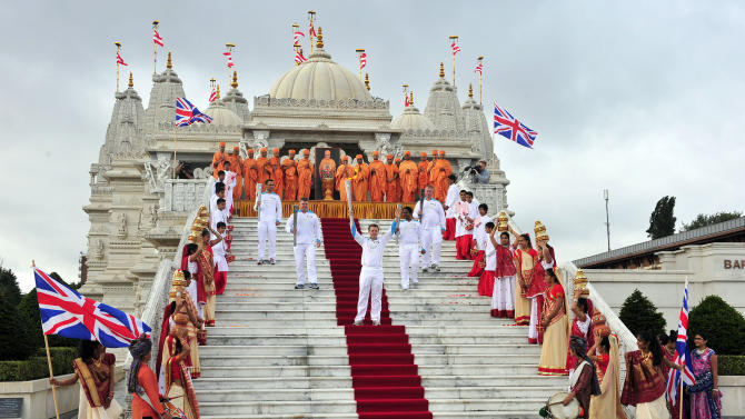 This photo made available by LOCOG shows Torchbearing team 056, (NOT left to right) including, Barrie Guy, Antony Eames, and others, no names available, outside the Shri Swaminarayan Mandir temple, in Brent, north London, as they carry the Paralympic Flame on the Torch Relay, Wednesday Aug. 29, 2012. (AP Photo/LOCOG, Ben Birchall)