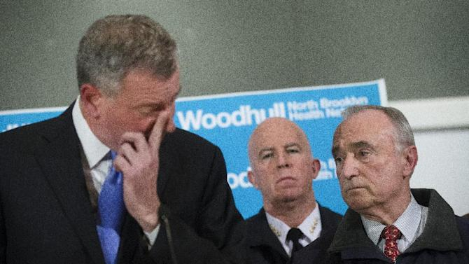 NYPD Commissioner Bill Bratton, right, stands beside Mayor Bill de Blasio as he wipes his eye during a news conference at Woodhull Medical Center, Saturday, Dec. 20, 2014, in New York.  An armed man walked up to two New York Police Department officers sitting inside a patrol car and opened fire Saturday afternoon, killing one and critically wounding a second before running into a nearby subway station and committing suicide, police said. (AP Photo/John Minchillo)