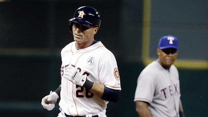 Houston Astros' Rick Ankiel (28) rounds the bases on a three-run home run as Texas Rangers' Adrian Beltre watches in the sixth inning of a baseball game, Sunday, March 31, 2013, in Houston. (AP Photo/Pat Sullivan)