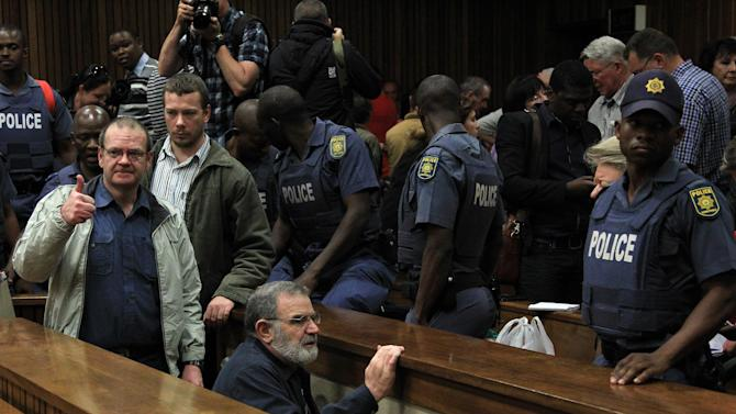 Accused member of Afrikaner extremist group Boeremag Tom Voster, front, and co-accused Andre du Toit, left, go down to the holding cells after their sentencing at High Court in Pretoria, South Africa, Tuesday, Oct. 29, 2013. A South Africa court handed members of a white extremist group sentences ranging from five to 35 years in prison, with years suspended, for various charges including high treason and murder in the country's first post-apartheid treason trial. (AP Photo/Themba Hadebe)
