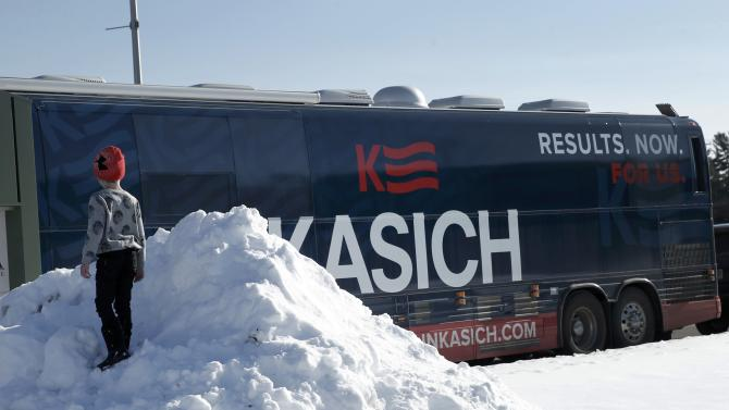 A young boy plays in a snowbank near the campaign bus of U.S. Republican presidential candidate John Kasich in Nashua