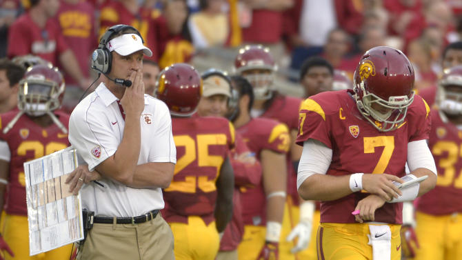FILE - In this Oct. 20, 2012, file photo, Southern California head coach Lane Kiffin, left, looks on as quarterback Matt Barkley walks on to the field during the second half of an NCAA college football game against Colorado in Los Angeles.  A student manager's dismissal for underinflating game balls is just the latest embarrassment for USC. Coach Lane Kiffin says he and quarterback Matt Barkley knew nothing about this. But Kiffin's gamesmanship has been evident in other parts of the Trojans' season.  (AP Photo/Mark J. Terrill, File)