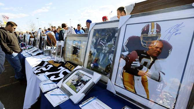 Fans look at sports memorabilia available in a silent auction held to raise money for people suffering the affects of Superstorm Sandy and cystic fibrosis before an NFL football game between the New York Giants and the Pittsburgh Steelers, Sunday, Nov. 4, 2012, in East Rutherford, N.J. (AP Photo/Julio Cortez)